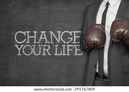 Change your life on blackboard with businessman wearing boxing gloves - stock photo