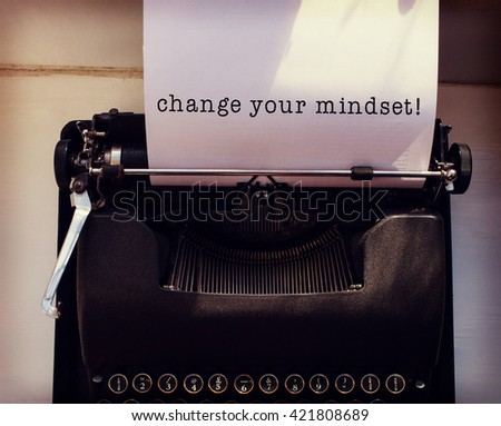 Change your mindset message on a white background against womans hand typing on typewriter - stock photo