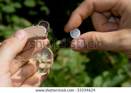 Changing a digital hearing aid battery. - stock photo