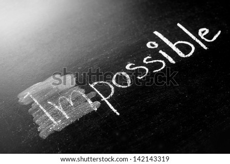 Changing impossible into possible on a chalkboard - stock photo