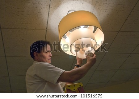 Changing light bulb in commercial building - stock photo
