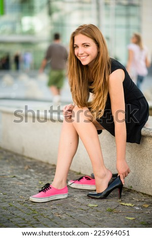 Changing shoes - teenager puts on high heels instead of sneakers on street - stock photo
