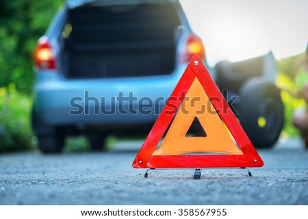 Changing the tire on a broken down car on a road with red warning triangle - stock photo
