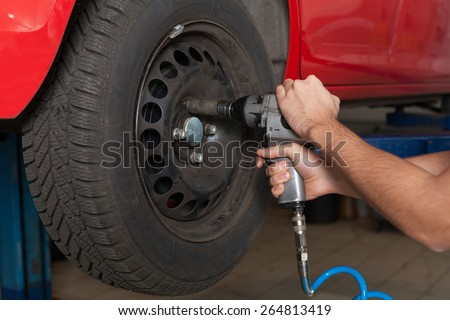 Changing the wheel with an impact wrench. Close up of man's hands changing wheel. Hands holding a impact wrench. - stock photo