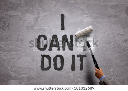 Changing the word can't to can by painting over and erasing part of it with a paint roller on a concrete wall in the phrase i can do it - stock photo