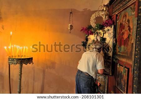 Chania, Crete Island, Greece, - August. 28. 2008: Man praying at Agios Ioannis church, old Greek Orthodox church, near Chania, Crete Island, Greece - stock photo
