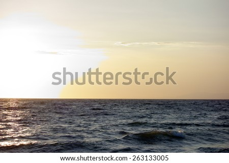 Channel Islands hidden in colorful yellow-brownish evening hour as seen from Mandalay Beach, Oxnard, California; backlit shot - stock photo