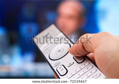 Channel surfing with remote control in hand and politics on - stock photo