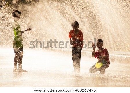 Chanthaburi (Thailand) - Apr 12, 2012. Children enjoy using  plastic water gun splashing water to  people passing them in the street with artificial water tunnel during Songkran Water Festival.