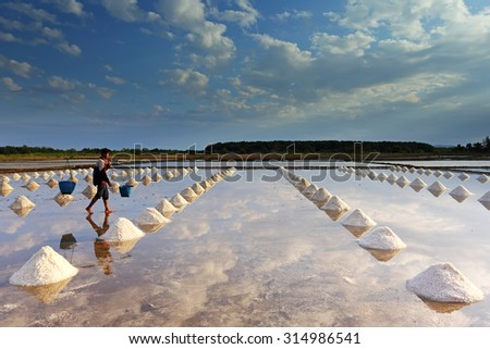 CHANTHABURI,THAILAND - JAN 13: Unidentified workers carrying salt at the salt farm on January 13, 2013 in Chanthaburi,Thailand. It is a salt production is one of a small industry of Chanthaburi - stock photo