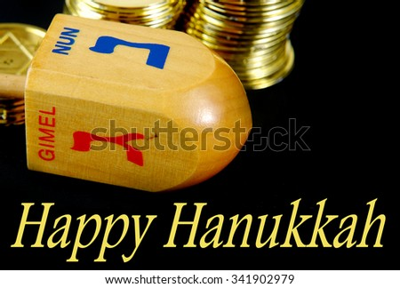 Chanukah, or Hanukkah image of wooden dreidel and gelt coins as token pieces for playing the game. All on a black background. Hanukkah message included. Colors are blue, gold and red.  - stock photo