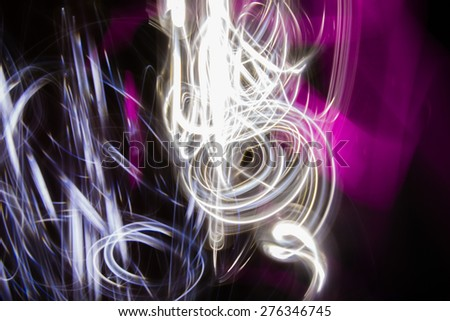 Chaos - Glowing abstract curved lines. Different colors. Black background. Done by long exposure technique