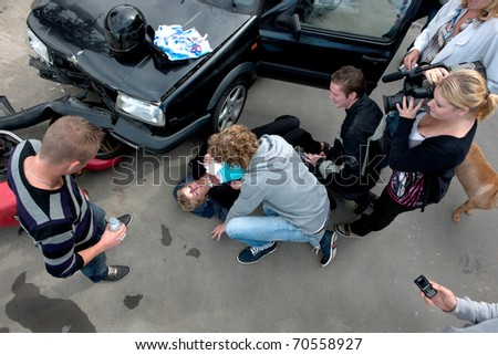 Chaotic scene just after a car crash, with an injured woman lying on the ground, several bystanders providing first aid, and a television reporter with camera capturing the scene, seen from above - stock photo