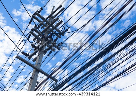 chaotic wire on concrete pole and cloudy blue sky