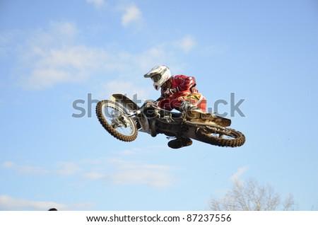 "CHAPAYEVSK, SAMARA, RUSSIA  - OCTOBER 17: Motocross racer I. Baranov in-flight with large horizontal tilt the Open Cup ""Volga"" motocross on October 17, 2011 in Chapayevsk, Samara, Russia - stock photo"