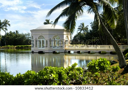 Chapel of Love on the Island of Kauai.  Reflection in still waters of lagoon.  Blue skies and leaning palm tree. - stock photo