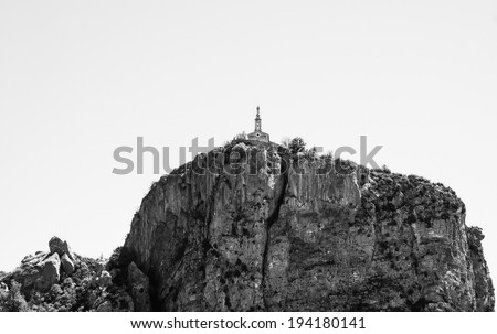 Chapel of Our Lady of the Rock with statue of the Virgin Mary holding Baby Jesus on the top of the rock in the medieval town Castellane (Provence, France). Aged photo. Black and white. - stock photo