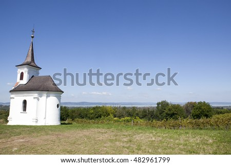 Chapel on hill overlooking vineyars in Latrany, Balatonlelle, Hungary with Lake Balaton in background