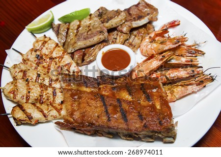 char-grilled short ribs, chicken strips, shrimps and BBQ pork ribs platter - stock photo