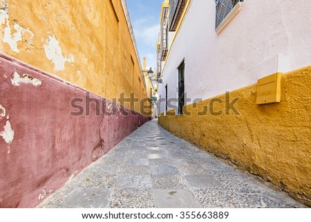 Characteristic colorful street in the old historical center of Seville, Spain, in the early morning with beautiful light and no people around - stock photo