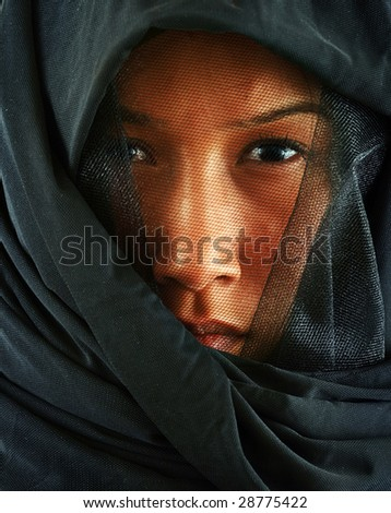 Characteristic emotional portrait of the beautiful young woman of east origin, the person is covered with a black veil