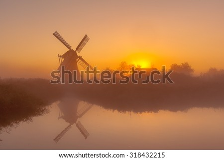Characteristic historic windmill along a wide canal in a polder wetland on a foggy september morning in the Netherlands - stock photo