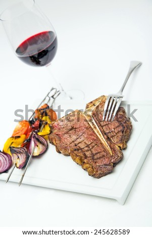 charbroiled steak with red wine and grilled vegetables on a plate,isolated on white, horizontal format - stock photo