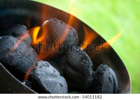 Charcoal briquettes firing up for the grill. - stock photo