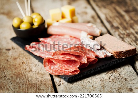 Charcuterie assortment and olives on wooden background - stock photo