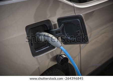 Charging an electric car at a roadside urban charging station showing a close up of the attached connector and cable in a green energy concept - stock photo