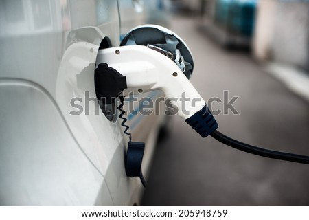 Charging an electric car with the power cable supply plugged in. - stock photo