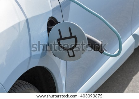 Charging an electric car with the power cable supply plugged in, closeup - stock photo