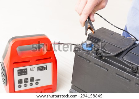 Charging car battery with digital multimeter - stock photo