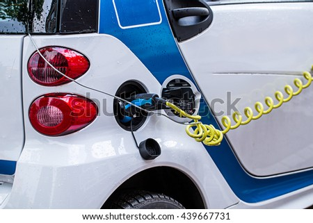 charging electric car on parking area. - stock photo