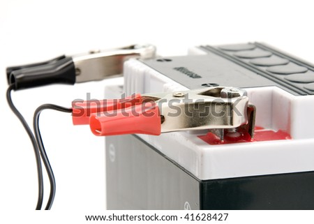 Charging motorcycle battery close up isolated on white background - stock photo
