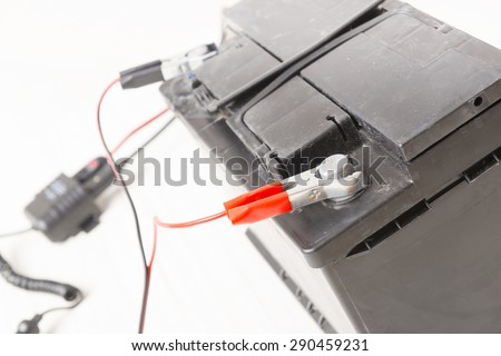 Charging old car battery at workshop - stock photo