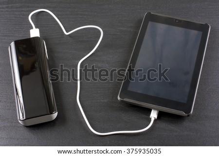 Charging tablet from portable rechargeable battery on black desk - stock photo