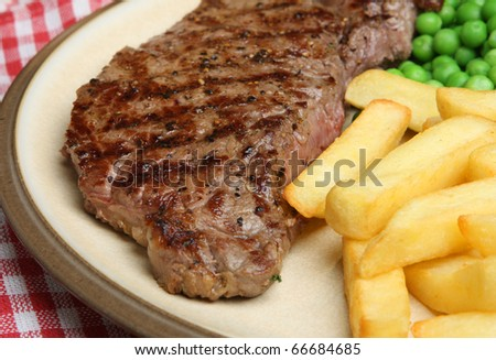 Chargrilled sirloin steak with chips and peas. - stock photo