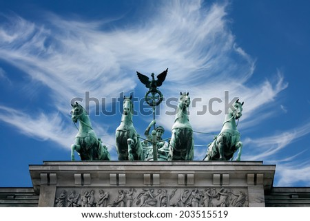 Chariot with the goddess of victory Victoria on the Brandenburg gate, Berlin, Germany, against the cloudy sky - stock photo