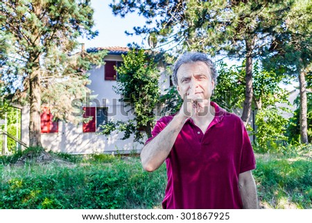 Charismatic and handsome Caucasian sportsman of forty with grey hair wearing red polo shirt and dark linen trousers invites you to be quiet with a finger over lips in a park in Emilia Romagna in Italy - stock photo