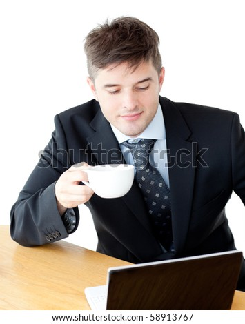 Charismatic businessman drinking coffee using his laptop at the breakfast table - stock photo