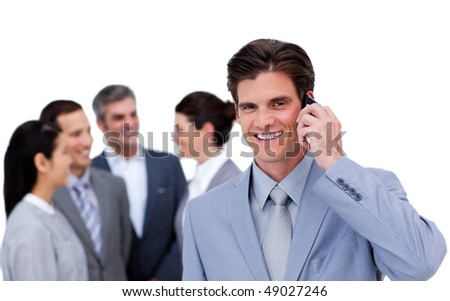 Charismatic businessman on phone standing apart from his team against a white background