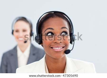 Charismatic businesswoman and her colleague with headset in a call center