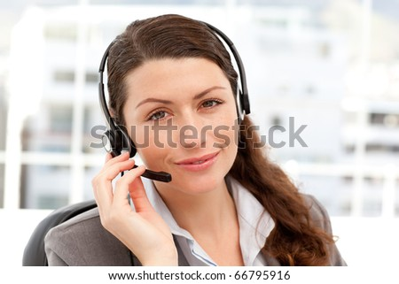 Charismatic businesswoman using earpiece sitting at her desk in her office