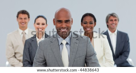 Charismatic Ethnic businessman with his team smiling at the camera - stock photo