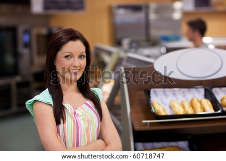 Charismatic female cook smiling at the camera in front of her bakery - stock photo