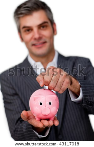Charismatic male executive saving money in a piggybank against a white background
