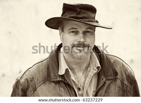 Charismatic  man with a hat and leather jacket. - stock photo