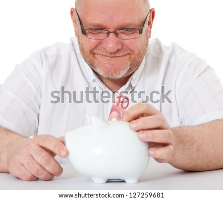 Charismatic middle aged man puts 10 euro into piggy bank. All on white background. - stock photo