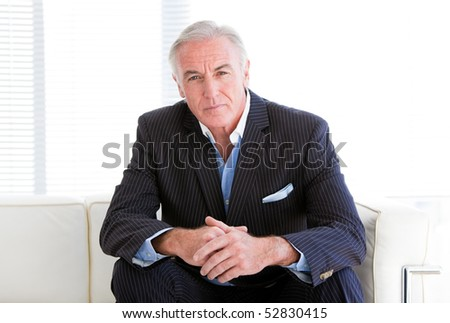 Charismatic senior businessman sitting on a sofa in the office - stock photo